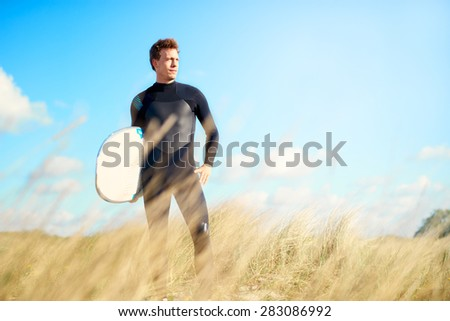 Surfer wearing his wetsuit with his surfboard under his arm standing on a dune looking at the ocean against a blue summer sky, with copyspace - stock photo