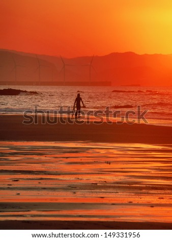 surfer with a boogie board entering sea at sunset - stock photo
