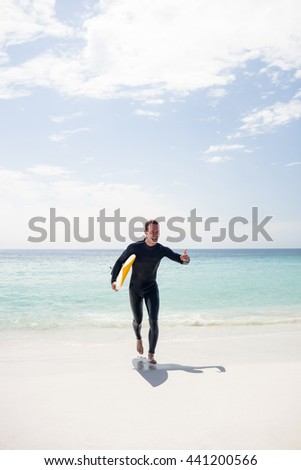 Surfer with a surfboard running on the beach on a sunny day - stock photo