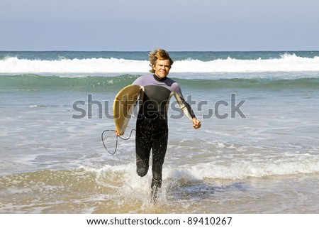 Surfer with his surfboard running out of the water from the atlantic ocean - stock photo