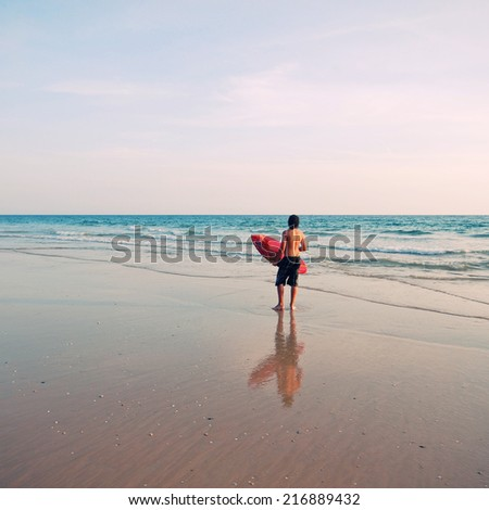 Surfer with surf board on sunrise ocean beach, Portugal. instagram effect, square image - stock photo