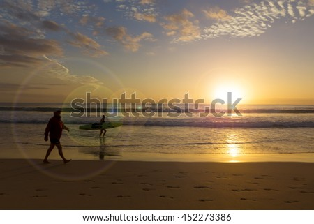 Surfer with surfboard in the sunrise scenery at Manly Beach,Australia-with sun glare and lens flare-vintage themes filter(intention) - stock photo