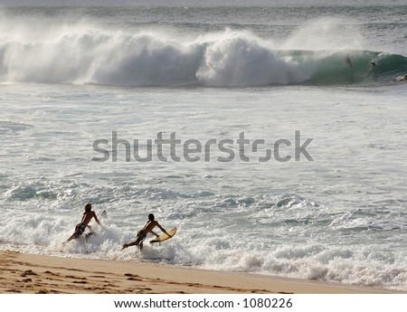 Surfers at Bonzai Pipeline off of Oahu's North Shore. (image contains noise) - stock photo