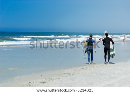 Surfers in a tropical white sand beach with turquoise waters