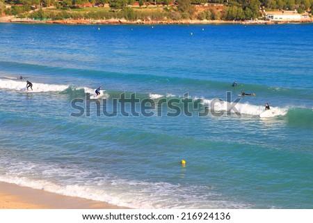 Surfers on a beach near the Aegean sea, Vouliagmeni, Greece - stock photo