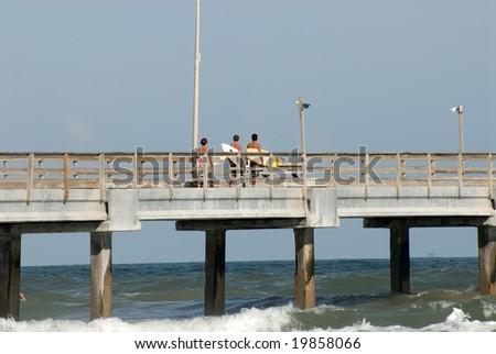 Surfers on the Bob Hall Pier on Padre Island, Texas USA - stock photo