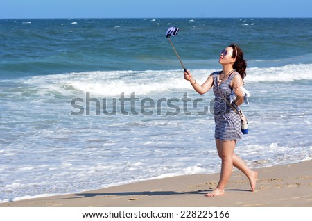 SURFERS PARADISE, AUS - NOV 01 2014:Asian woman take selfie photo on the beach. Over 1 Million selfies Are taken each day.Instagram has over 53 million photos tagged with the hash tag #selfie.