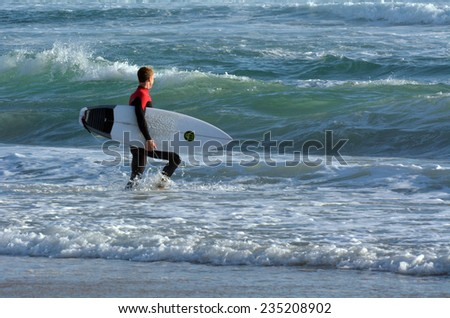 SURFERS PARADISE, AUS - OCT 14 2014: Surfer get into the water of Main beach.It is a very popular surfing beach in Surfers Paradise Gold Coast Queensland, Australia. - stock photo