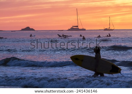 Surfers silhouetted against a brillinatly colored sunset  on Playa Tamarindo, Guanacaste, Costa Rica