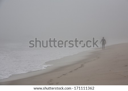 Surfers survey the scene as waves crash on a Cape Cod beach during a foggy morning. Waves and wind, in association with sea level rise, are eroding many coastlines throughout the world. - stock photo