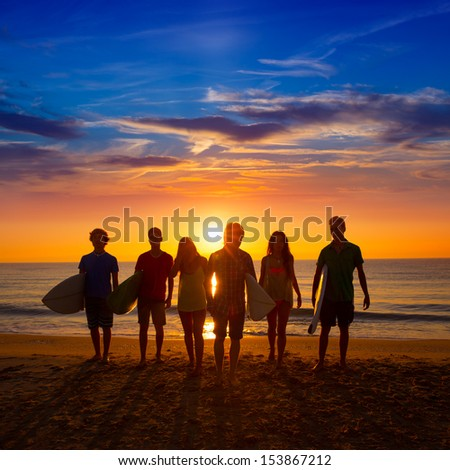 Surfers teen boys and girls group walking on beach at sunshine sunset back light