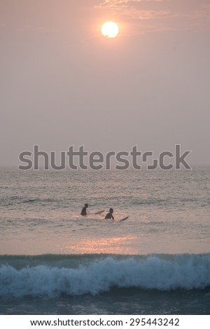 Surfers wait for a set of waves off the coast of Cape Cod, Massachusetts. The beaches of Cape Cod provide a nice place to learn to surf though Great White sharks hunt seals in these same waters. - stock photo