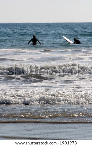 Surfers wait for waves. - stock photo