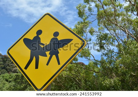 Surfers with surfboards crossing sign. - stock photo