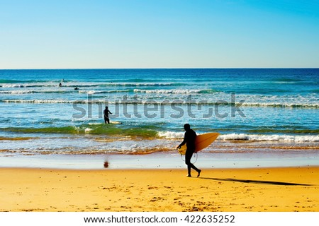Surfers with surfboards going to the ocean in a bright sunny day - stock photo