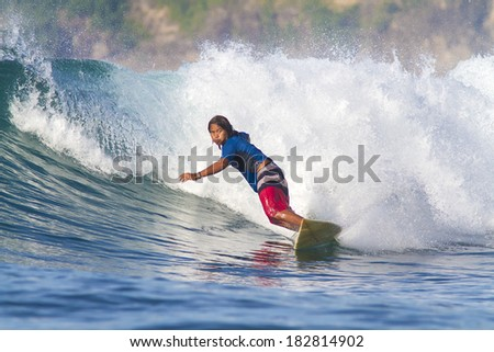 surfing a wave in Indonesia