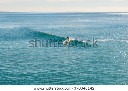 Surfing at Daytime. Young Man Riding Wave at Sunset.  - stock photo