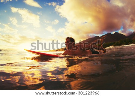 Surfing at Sunset. Outdoor Active Lifestyle. - stock photo
