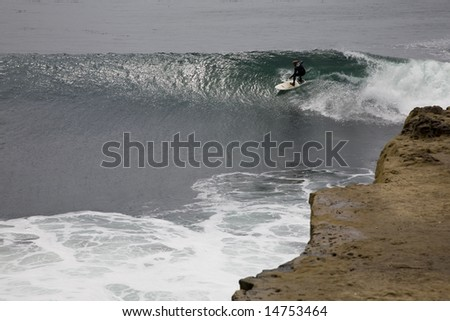 Surfing close to the dangerous rocky coast.