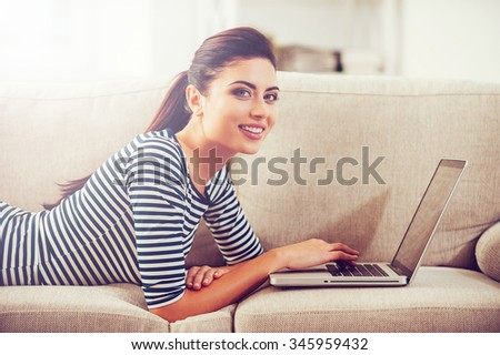Surfing the net at home. Beautiful young woman working on laptop and smiling while lying on the couch at home  - stock photo