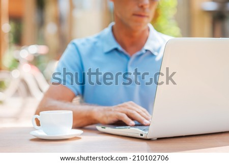 Surfing the net in cafe. Close-up of confident mature man writing something in his note pad and smiling while sitting at the table outdoors with house in the background  - stock photo