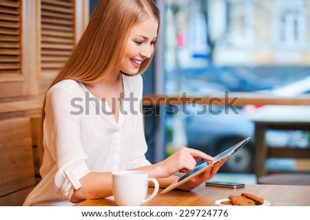 Surfing the net in cafe. Side view of beautiful young woman using digital tablet and smiling while enjoying coffee in cafe - stock photo