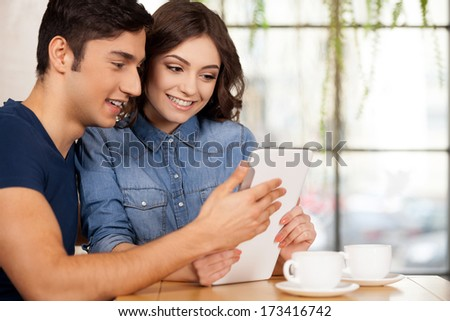 Surfing the net together. Beautiful young couple sitting together at the restaurant and using digital tablet - stock photo