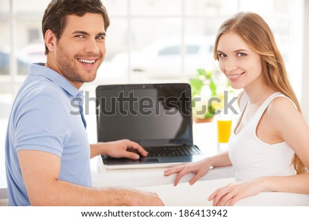 Surfing the net together. Handsome young man sitting at the table and using laptop while his girlfriend standing behind him