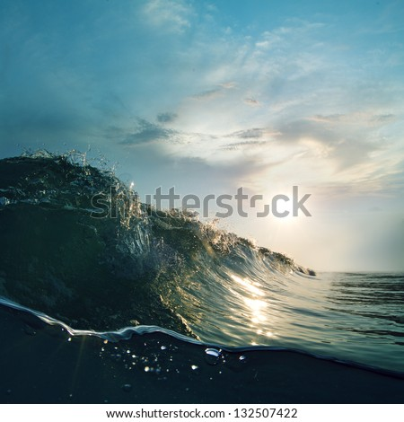 Surfing tropical design template. Green blue colored ocean surfing wave breaking and splashing at sunset time - stock photo