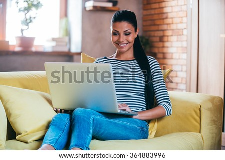 Surfing web at home. Beautiful young woman working on laptop and smiling while sitting on the couch at home  - stock photo