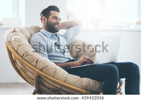 Surfing web at home. Handsome young man working on laptop and smiling while sitting in big comfortable chair at home