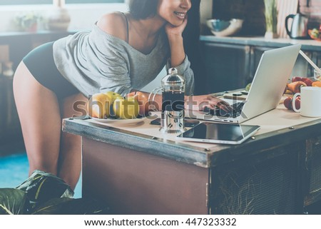 Surfing web from kitchen. Close-up of attractive young African woman leaning at the kitchen desk and looking at laptop with smile  - stock photo