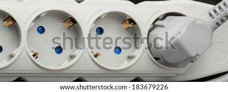 surge protector, electric outlet on a dark background - stock photo
