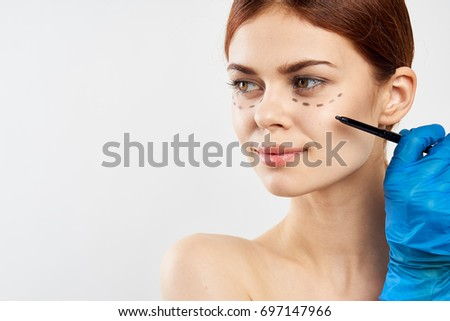 Surgeon draws on female lines before plastic surgery on light background