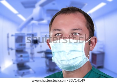 surgeon in operating room with mask - stock photo