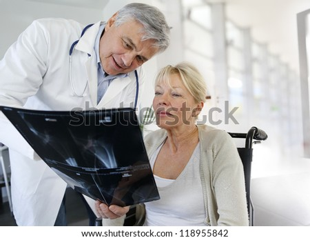 Surgeon showing X-ray result to woman in wheelchair - stock photo