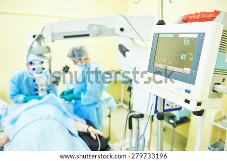 surgeon team in uniform in front of eye vision surgery operation room at medical clinic - stock photo