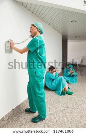 Surgeon using the phone in hospital corridor with two surgeons sitting on floor - stock photo