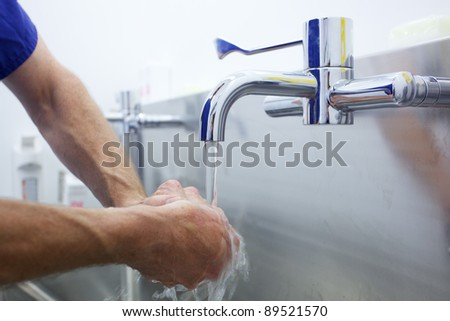 Surgeon washing hands prior to operation using correct technique for cleanliness - stock photo