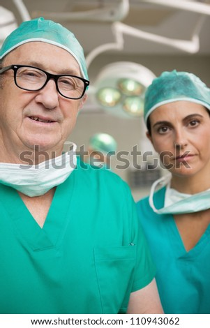 Surgeon with glasses on and a colleague in a surgical room