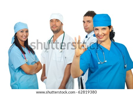 Surgeon woman showing okay sign in front of her team of doctors isolated on white background - stock photo