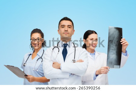 surgery, profession, people and medicine concept - group of medics with x-ray over blue background - stock photo