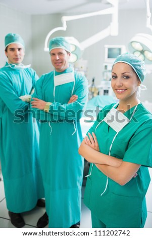 Surgical team standing up with arms crossed in an operating theater - stock photo