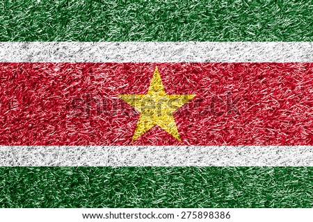Suriname flag on grass background texture - stock photo