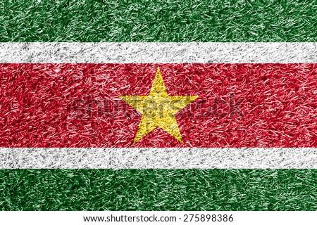Suriname flag on grass background texture - stock photo