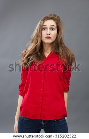 surprise and disappointment concept - portrait of a 20's brunette woman with messy hair expressing confusion putting down both arms and shoulders down for fear,studio shot - stock photo