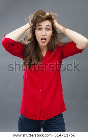surprise and disappointment concept - portrait of a smiling 20's brunette woman mess up her hair expressing confusion for amazement,studio shot - stock photo
