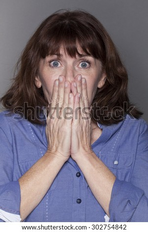 surprise and fear concept - attractive mature woman hiding her mouth with both hands looking stunned and anxious with eyes wide opened,closeup in studio shot - stock photo