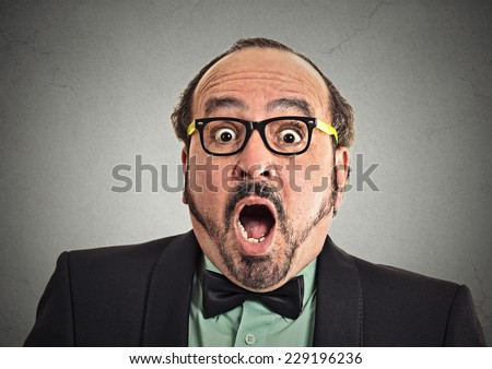 Surprise astonished man. Closeup portrait man looking surprised in full disbelief wide open mouth isolated grey wall background. Positive human emotion facial expression body language. Funny guy - stock photo