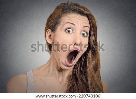 Surprise astonished woman. Closeup portrait woman looking surprised in full disbelief  wide open mouth isolated grey wall background. Positive human emotion facial expression body language. Funny girl - stock photo